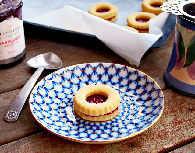 A single homemade jammie dodger sits on a blue and white plate next to a heart-shaped spoon and a mug of tea. A jar of jam and a tray of jammiedodgers are in the background.