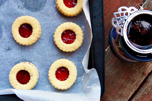 Overhead view of homemade jammie dodgers on a parchment-lined baking tray next to a cup of tea with a Victorian tea infuser.