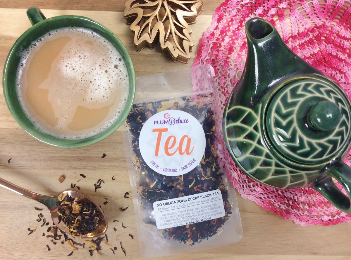 Overhead view of a package of Plum Deluxe loose leaf tea, a matching green teapot and teacup, and a spoon full of loose leaf tea arranged on a wooden table and pink doily.