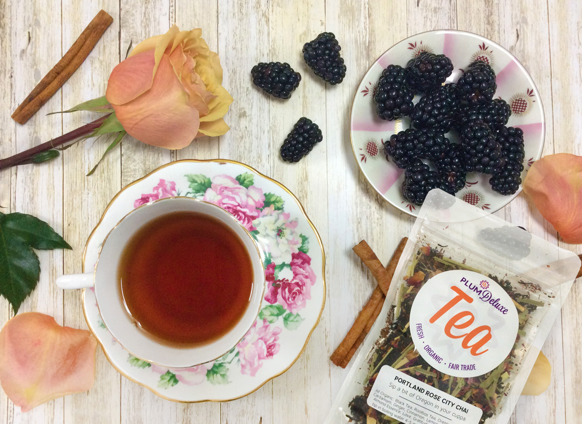 Overhead view of a rose teacup full of chai, a peach rose and rose petals, a dish of blackberries, cinnamon sticks, and a bag of Plum Deluxe Portland Rose City Chai.