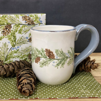 A white mug with a pine bough and pinecone motif and a blue handle sits on a green napkin surrounded by pinecones in front of its decorative printed gift box.