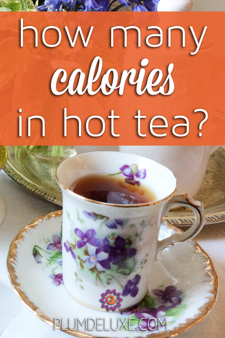 A white teacup with purple violets painted on it sits in front of a white teapot and vase of flowers. The overlay text reads: how many calories in hot tea?