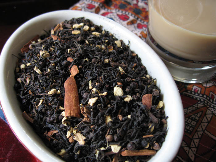 A bowl of loose leaf chai tea and spices sits on a patterned cloth next to a clear glass cup of brewed chai.