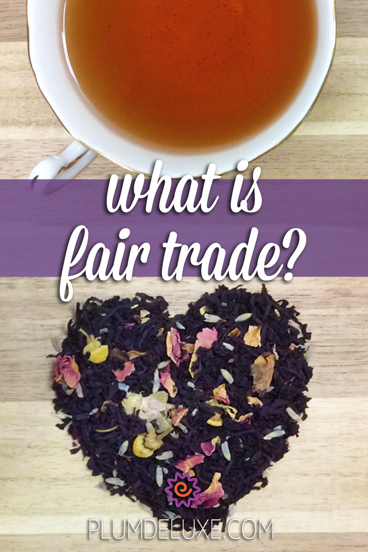 Overhead view of a cup of tea and a pile of loose leaf tea in the shape of a heart on a wooden table. The overlay text reads: what is fair trade?