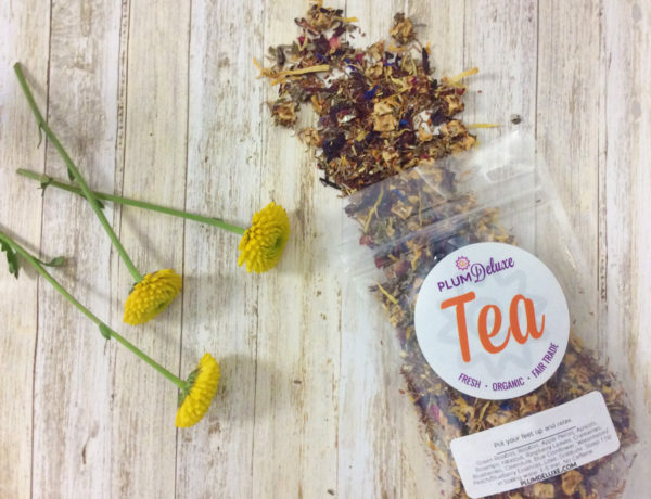Overhead view of a bag of loose leaf fair trade tea next to three yellow flowers on a wooden surface.