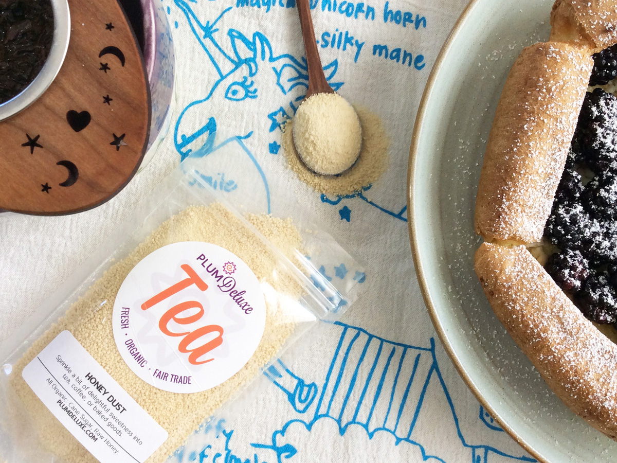 Overhead view of a package of honey dust, a wooden spoon full of honey dust, a teacup with cherrywood infuser, and a dutch baby pancake arrange on a unicorn tea towel.
