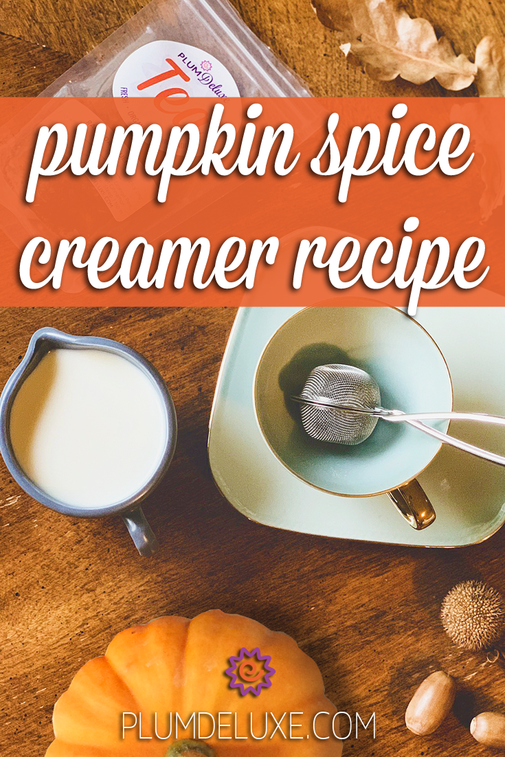 Overhead view of a pitcher of cream, a pumpkin, teacup and saucer with infuser, and a bag of loose leaf tea on a wooden table. The text overlay reads: pumpkin spice creamer recipe.