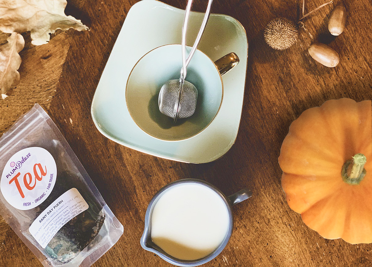 Overhead view of a pitcher of pumpkin spice creamer, a pumpkin, teacup and saucer with infuser, and a bag of loose leaf tea on a wooden table.