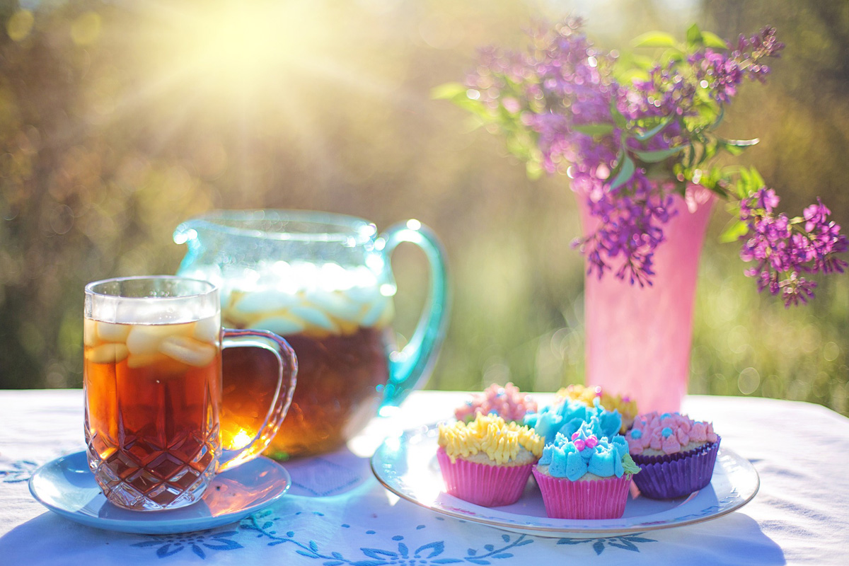A plastic pitcher and mug, both filled with iced tea, sit next to a plate of colorful cupcakes and a vase of flowers.