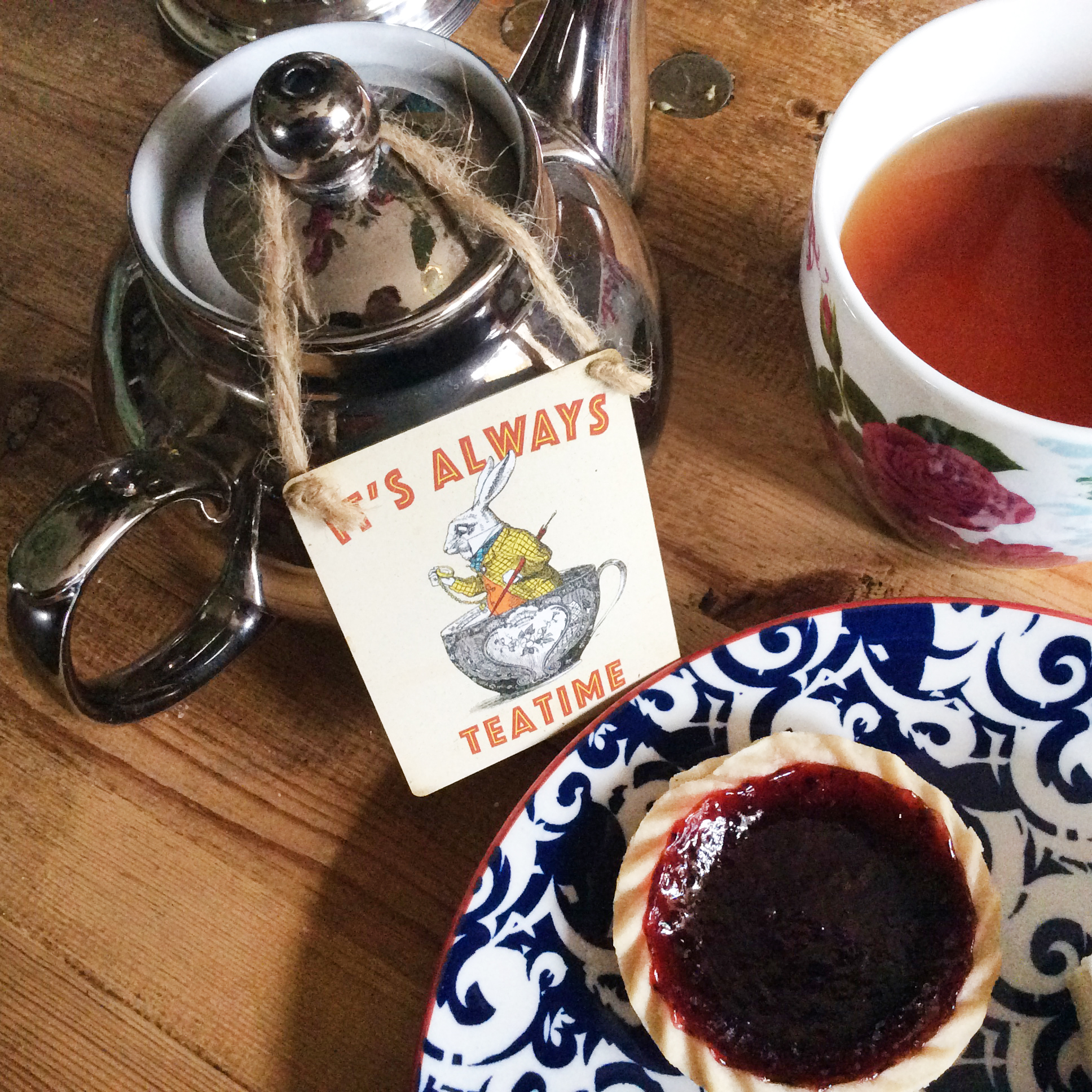 "A silver teapot has a tag around it that says ""it's always teatime"" with a picture of the White Rabbit from Alice in Wonderland. Next to it sits a blue and white floral plate with a jam tart and a cup full of tea."