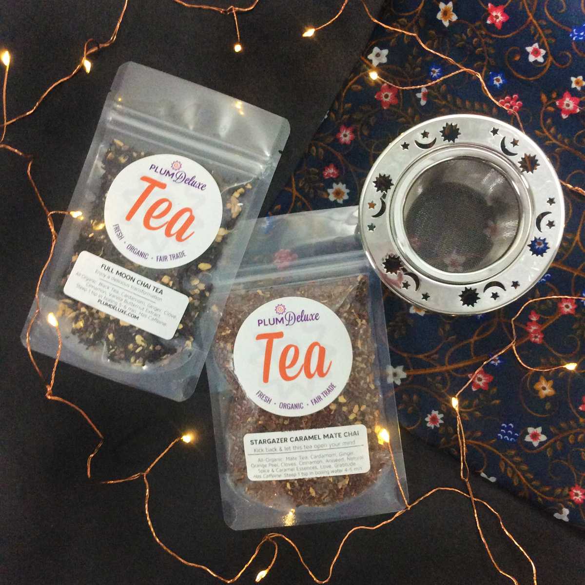 Overhead view of two bags of Plum Deluxe loose leaf tea and a celestial metal tea infuser on a dark blue floral cloth surrounded by twinkle lights.