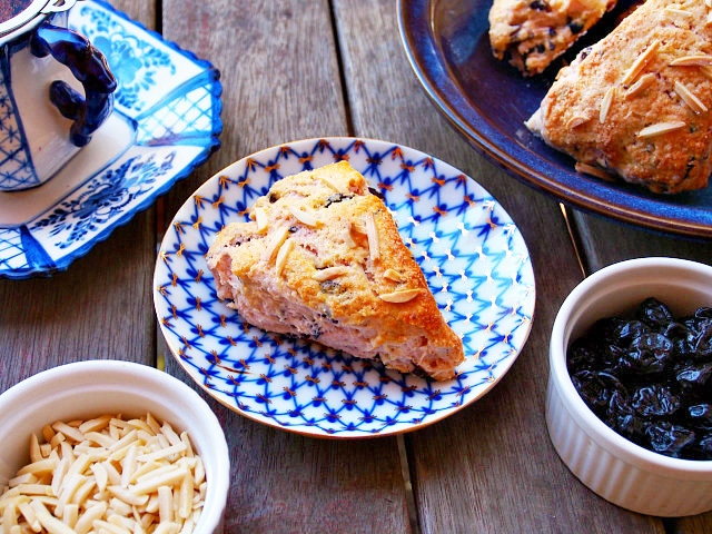 A single almond cherry scone sits on a blue and white plate on a wooden table. It is surrounded by another plate of scones, a white and blue teacup and saucer, and white dishes with dried cherries and slivered almonds.