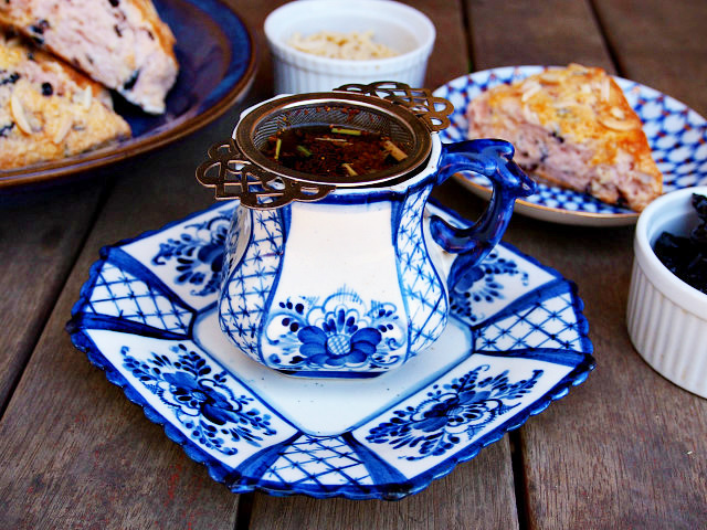 A white and blue teacup and saucer with a Victorian metal nest infuser sits on a wooden table. Two blue plates of almond cherry scones and white bowls of dried cherries and slivered almonds are in the background.