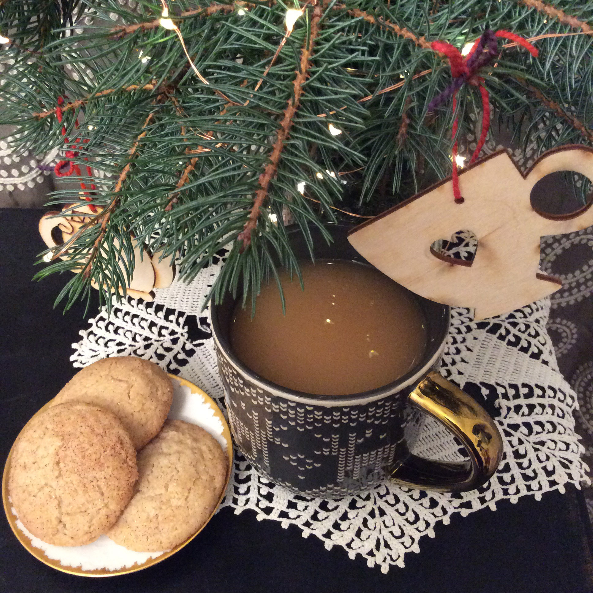 A sweater print mug of tea and a plate of snickerdoodles are arranged on a white lace doily under a pine tree decorated with twinkle lights and teacup ornaments.