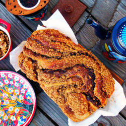 Overhead view of a loaf of cinnamon babka bread surrounded by a blue teapot, red floral plate, small red crock of walnuts, and teacup with cherrywood tea next infuser on a wooden table.