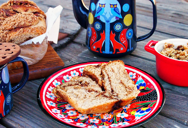 A slice of cinnamon babka sits on a red floral plate next to a small red crock of walnuts, a dark blue teapot with foxes painted on it, and the rest of the loaf of babka. All are arranged on a wooden table.