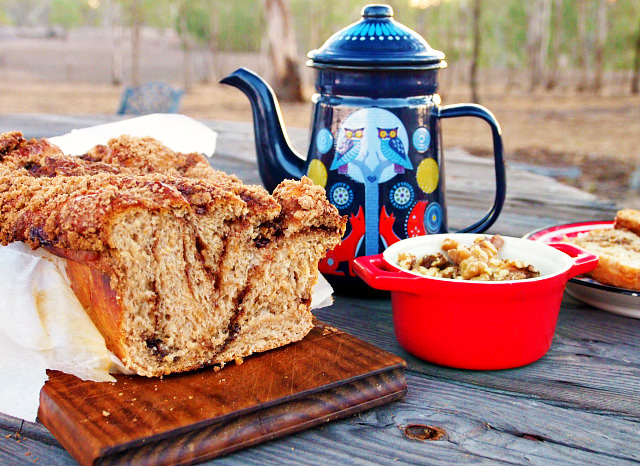 Side view of a loaf of cinnamon babka bread with a slice cut from the end. It sits on a wooden board next to a small red crock of walnuts and a dark blue teapot with foxes painted on it.