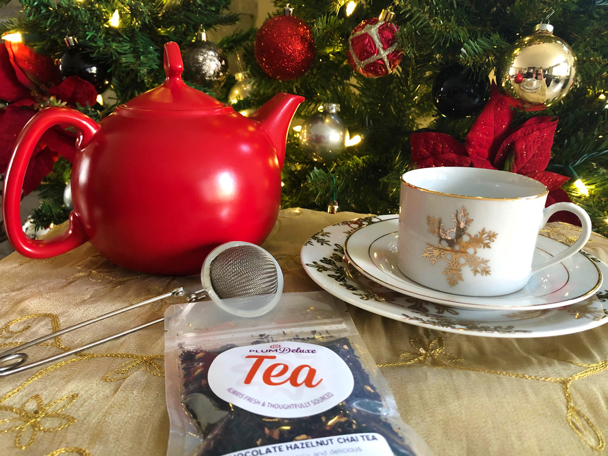 A red teapot, white teacup with a gold snowflake, and a bag of Plum Deluxe loose leaf tea are arranged on a gold tablecloth. In the background are evergreen boughs decorated with lights and red and gold ornaments.