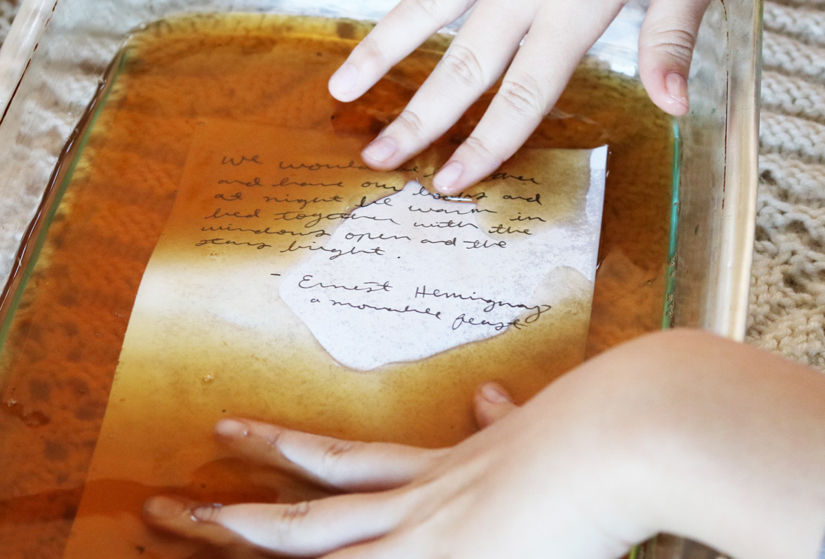 Two hands push a sheet of paper into a shallow dish of tea.
