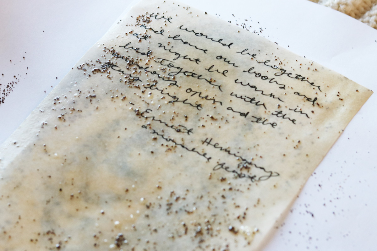 Tea leaves are sprinkled on a sheet of tea stained paper while it dries.