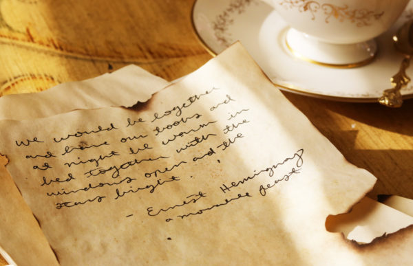 A quote from Ernest Hemingway is written in cursive on a sheet of tea stained paper. A teacup full of black tea sits next to it.