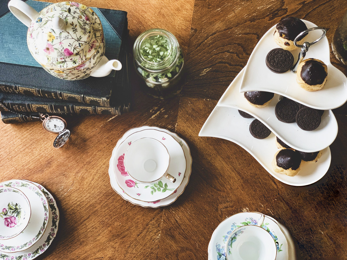 Overhead view of a tablescape for an Alice in Wonderland tea party featuring floral print teacups, a floral teapot, old books, a pocket watch, tiny terrarium with white rabbit figurines, and a tiered plate full of desserts.