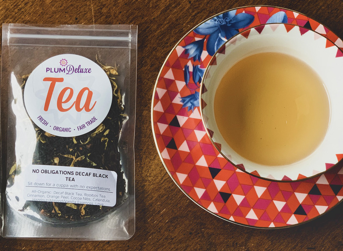 A bag of Plum Deluxe No Obligations Decaf Tea sits to the left of a red and blue floral teacup and saucer on a wooden table.