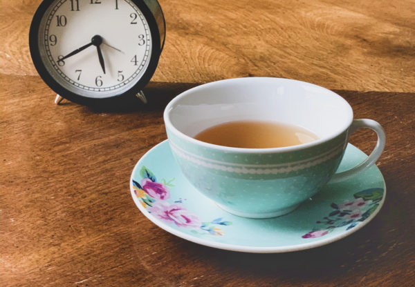 A light blue teacup and saucer full of tea sits on a wooden table. An old fashioned alarm clock is in the background.