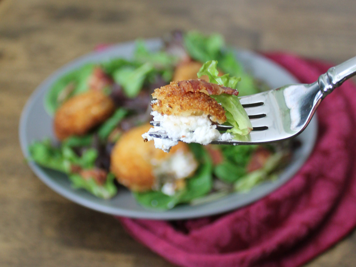 A fork holds a bite of fried goat cheese. Blurred in the background is a plate full of fried goat cheese on a bed of baby greens. A dark pink cloth sits to the right side.