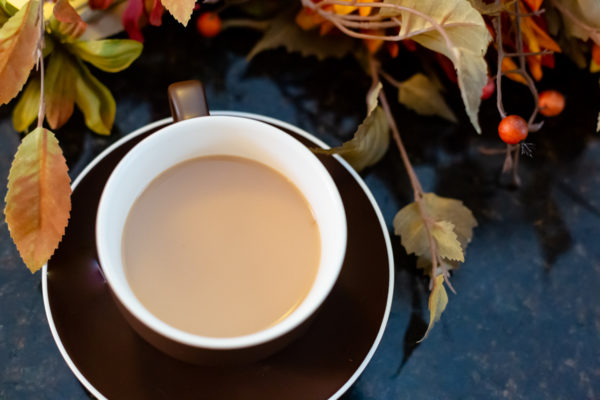 A brown teacup and saucer full of chai made in the instant pot sits in front of a file of fall foliage.