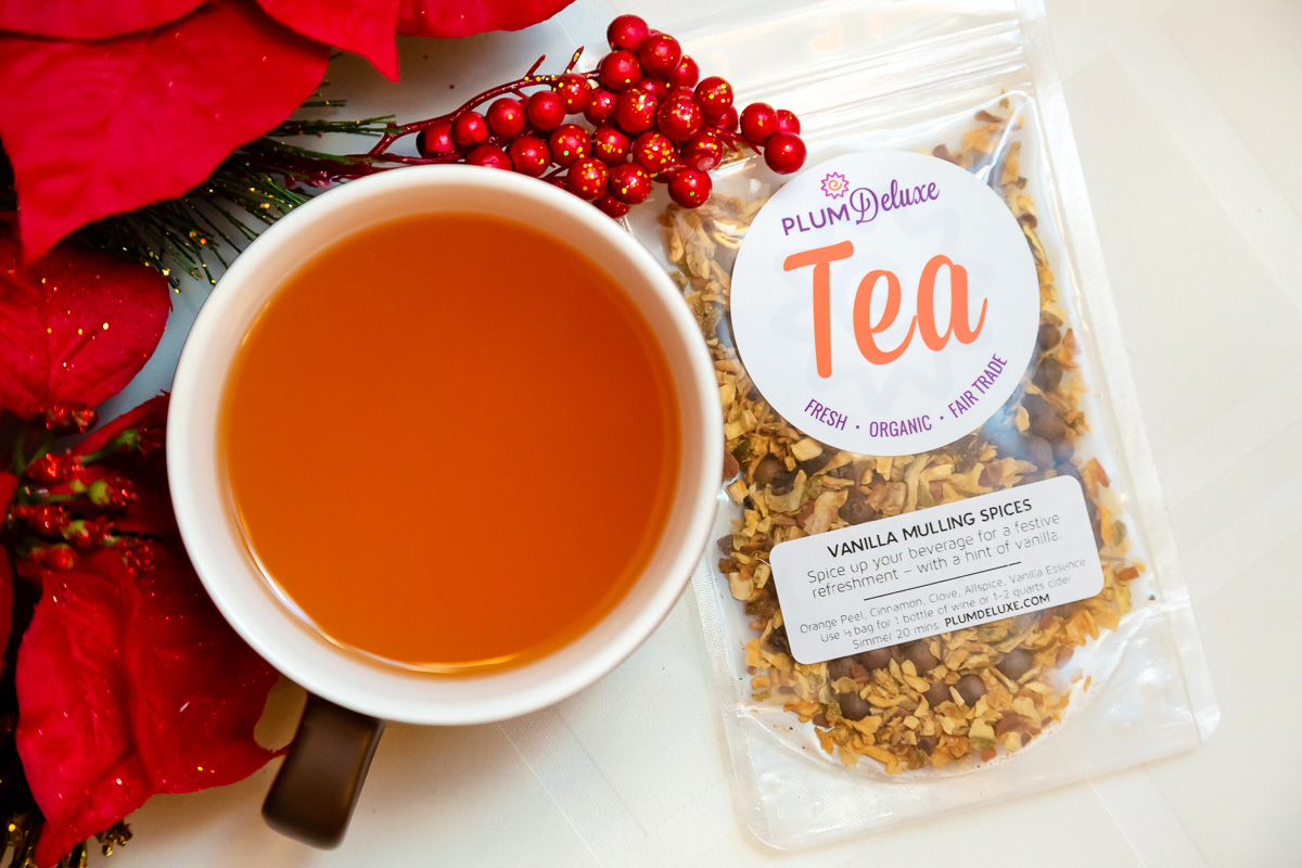 Overhead view of a mug of mulled apple cider and a bag of vanilla mulling spices on a white cloth. A red poinsettia is tucked to the side of the mug.
