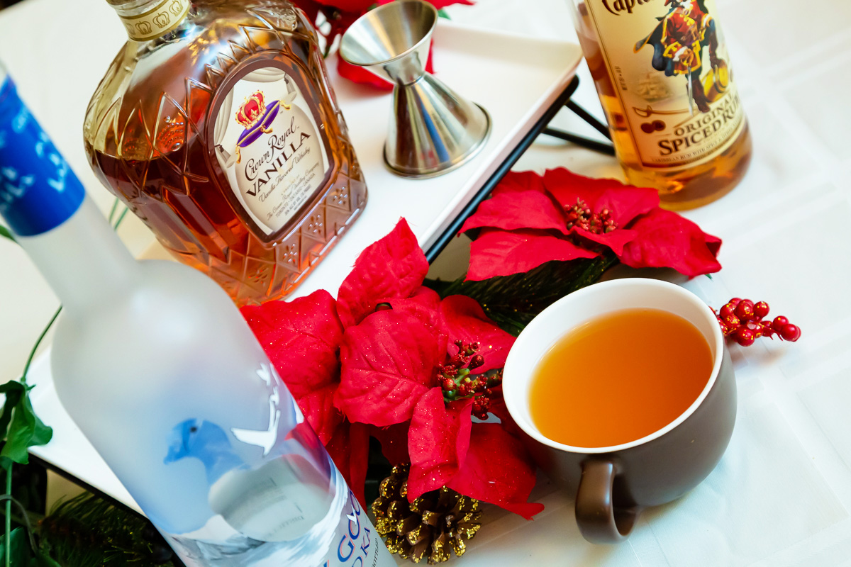 A mug of mulled apple cider sits next to a collection of various alcohol bottles and a trio of red poinsettias on a white tablecloth.