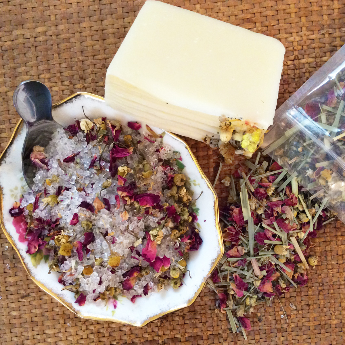 Overhead view of bath tea with rose petals, chamomile, lavender, and epsom salts in a dish with a silver scoop. A bar of soap rests next to it.