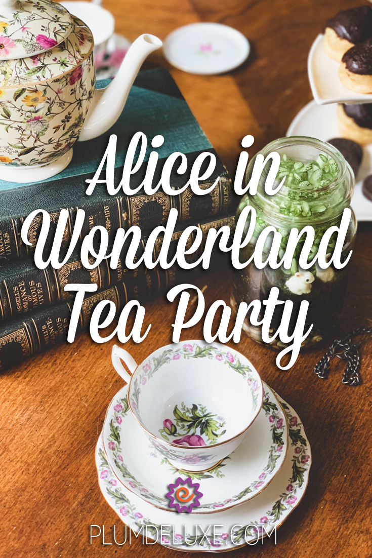 A white and floral teacup and saucer set sits in front of a stack of old books, a floral print teapot, and a small terrarium with white rabbit figurines. The overlay text reads: Alice in Wonderland Tea Party.