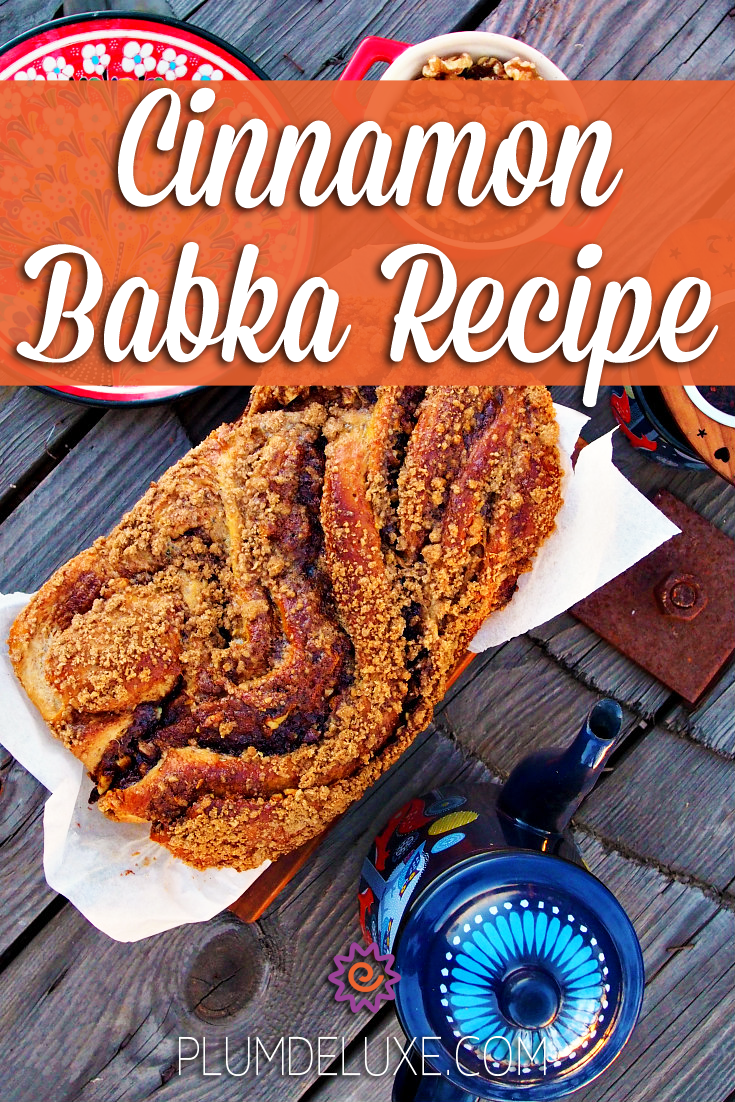 Overhead view of a loaf of cinnamon babka displayed on a wooden table next to a blue teapot. The overlay text reads: cinnamon babka recipe.