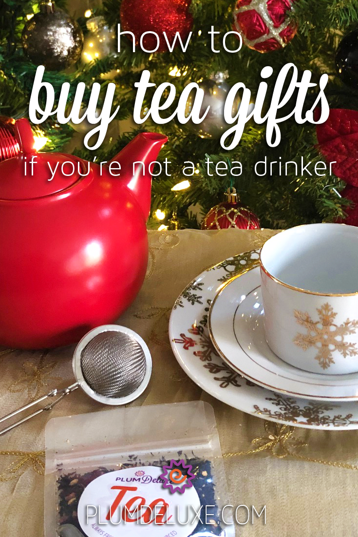 A red teapot and a white teacup with a gold snowflake on it sit on a gold tablecloth along with a mesh tea infuser and package of Plum Deluxe loose leaf tea. Evergreen boughs decorated with lights and ornaments are in the background. The overlay text reads: how to buy tea gifts if you're not a tea drinker.