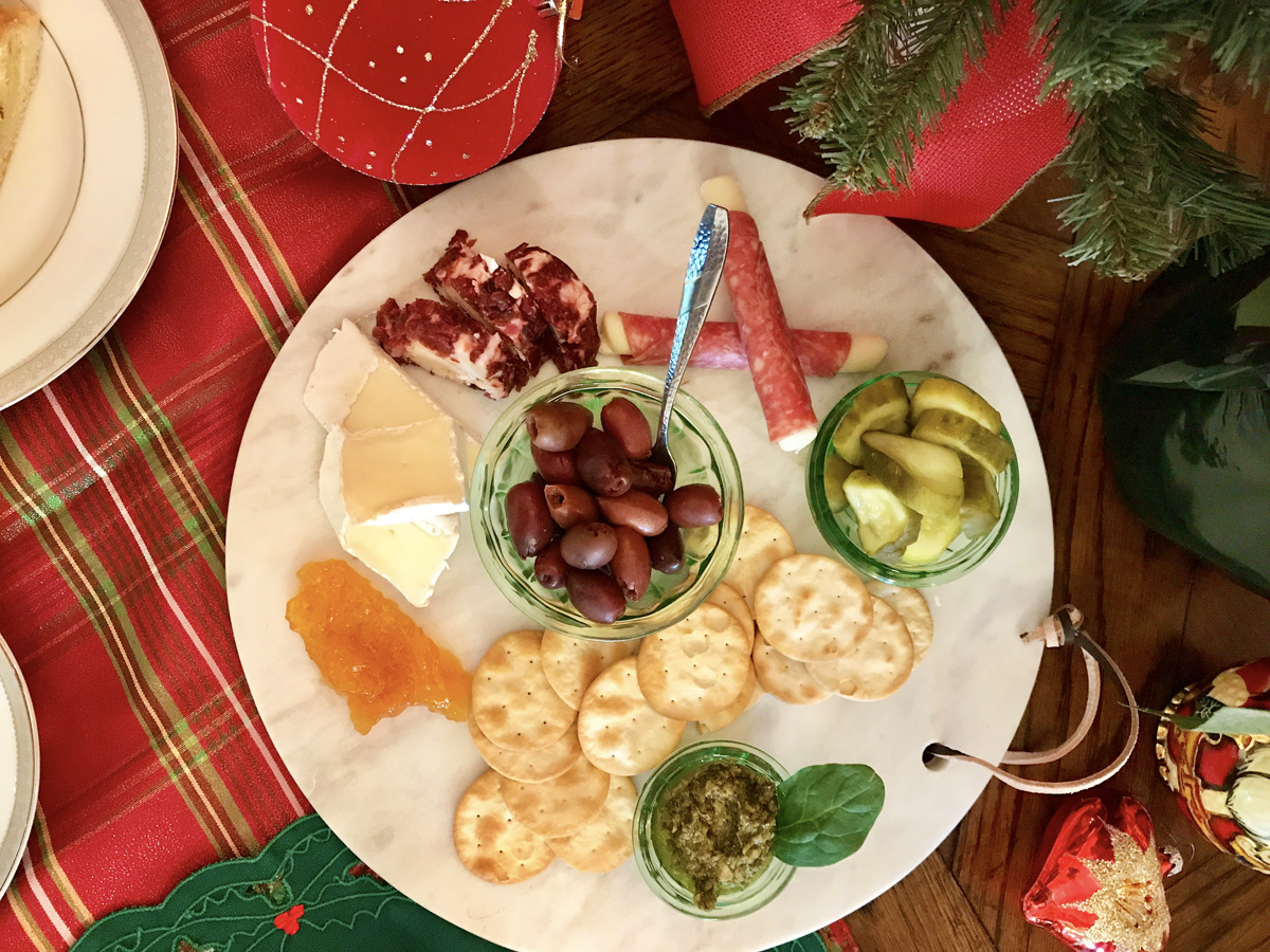 Overhead view of a charcuterie plate featuring meats, cheeses, pickles, crackers, nuts, and fruits on a red and green plaid tablecloth.