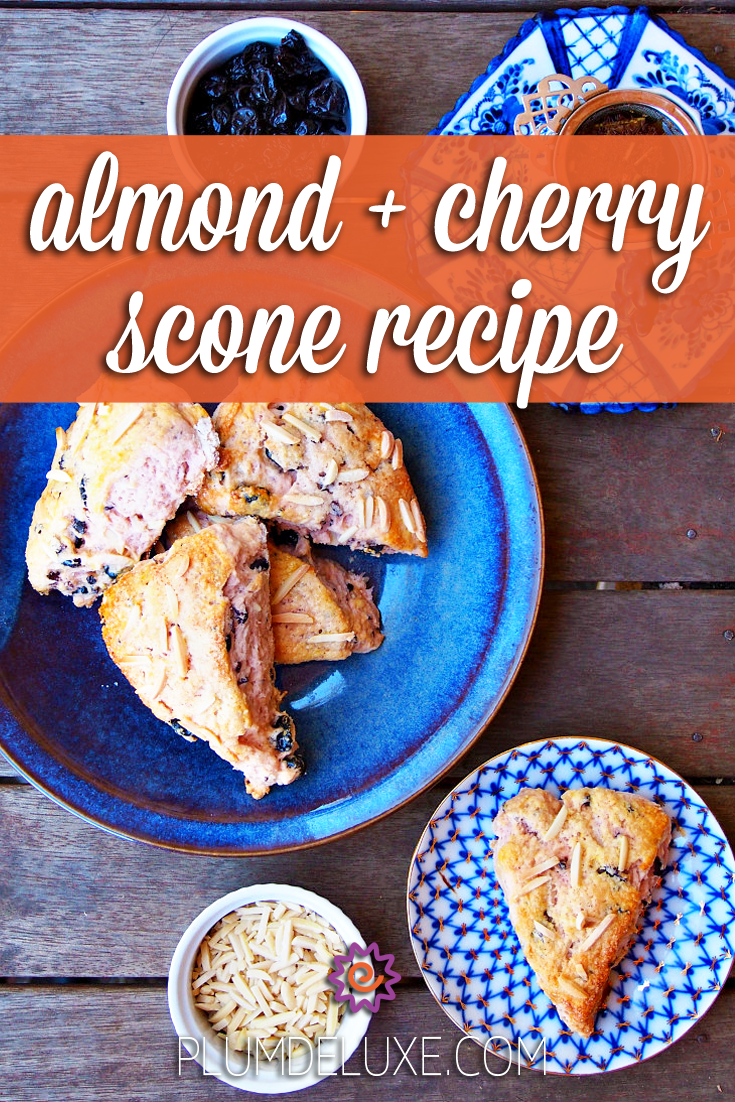 Overhead view of a blue plate piled with almond cherry scones on a wooden table. It's surrounded by a bowl of slivered almonds, a blue and white plate with a single scone, a blue and white cup of tea with victorian metal tea infuser, and a bowl of dried cherries. The overlay text reads: almond + cherry scone recipe.