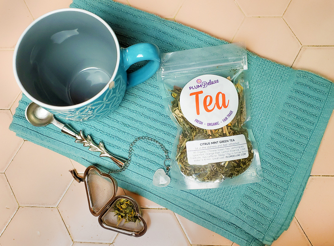 Overhead view of a blue mug, aqua towel, bag of loose leaf green tea, and a heart-shaped tea infuser on a pale tile background.