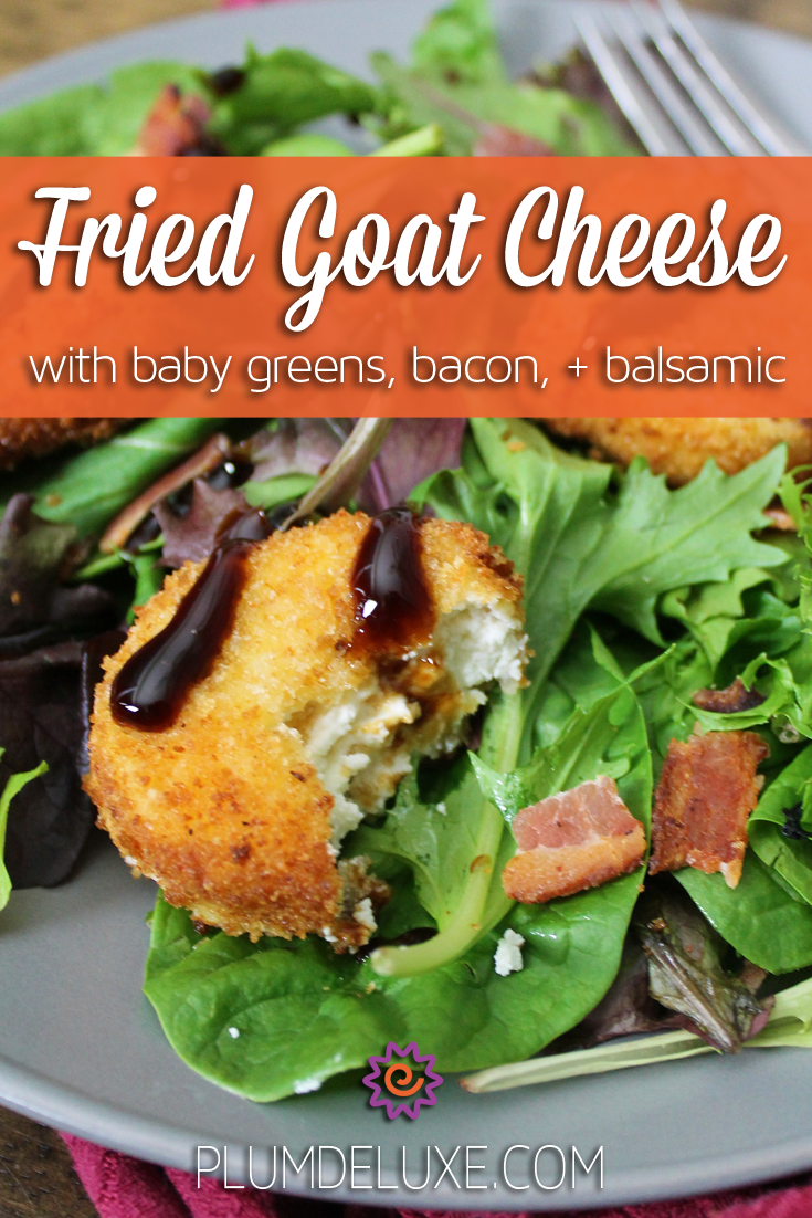 Closeup of a disc of fried goat cheese on a bed of greens with bacon and balsamic glaze. The overlay text reads: fried goat cheese with baby greens, bacon, + balsamic.