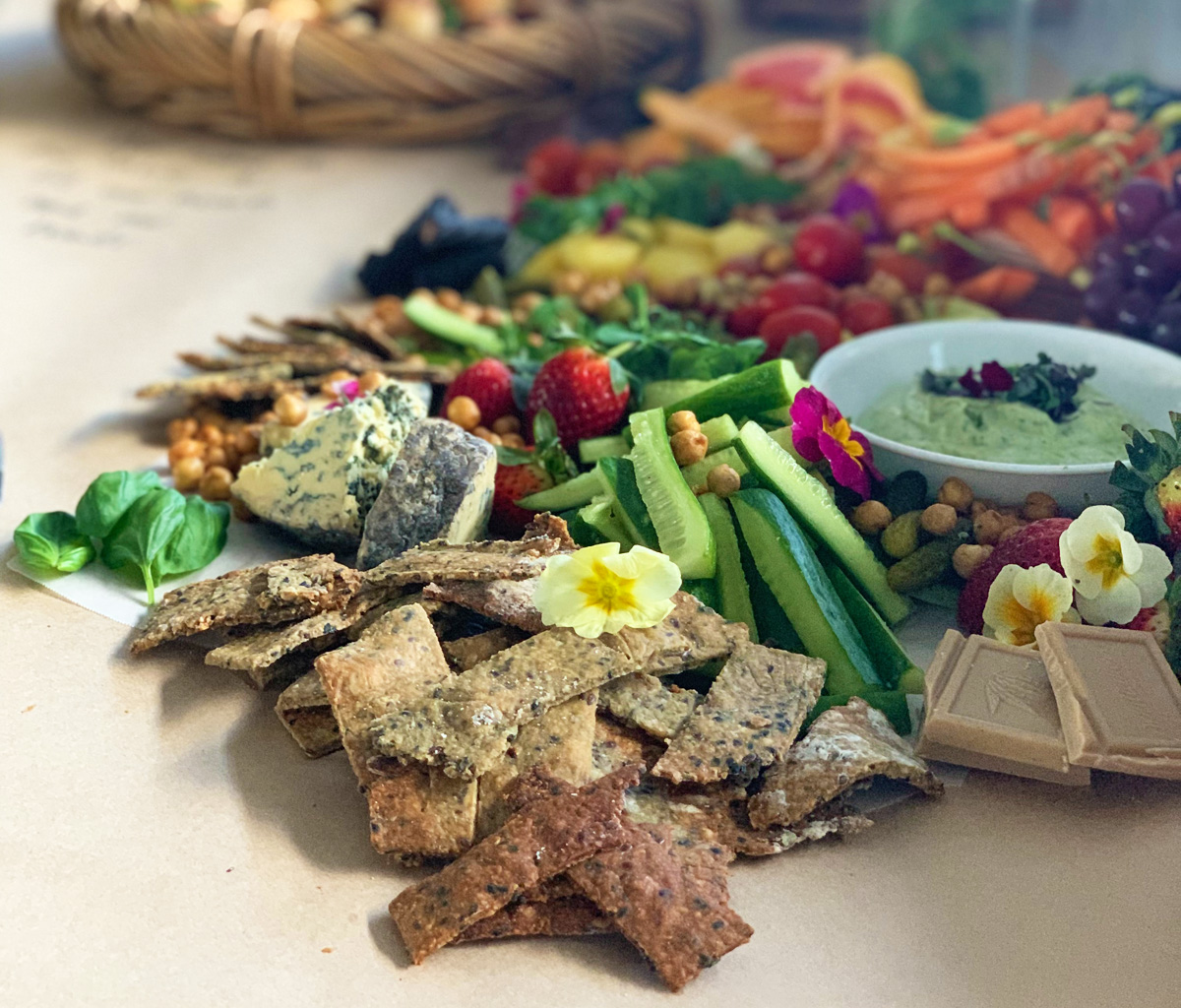 A grazing table covered in butcher paper is laden with vegetables, crackers, herbs, and cheeses.