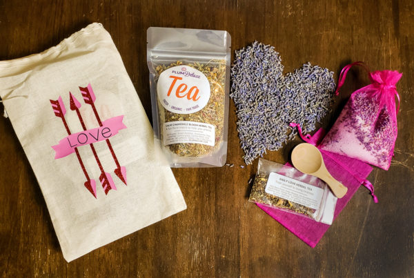Overhead view of ingredients for bath tea, including loose leaf tea, salt, mesh bags, and a pile of lavender in the shape of a heart, all displayed on a wooden table.
