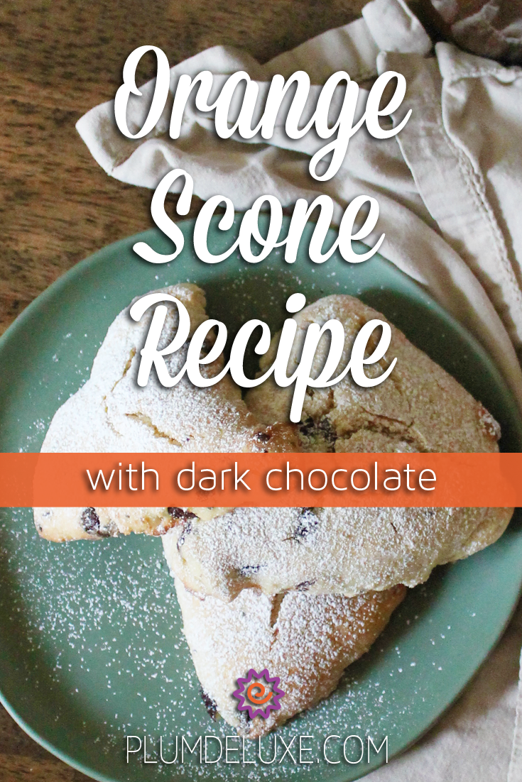 Three orange scones are piled on a light blue plate surrounded by a light colored tea towel. The overlay text reads: orange scone recipe with dark chocolate.