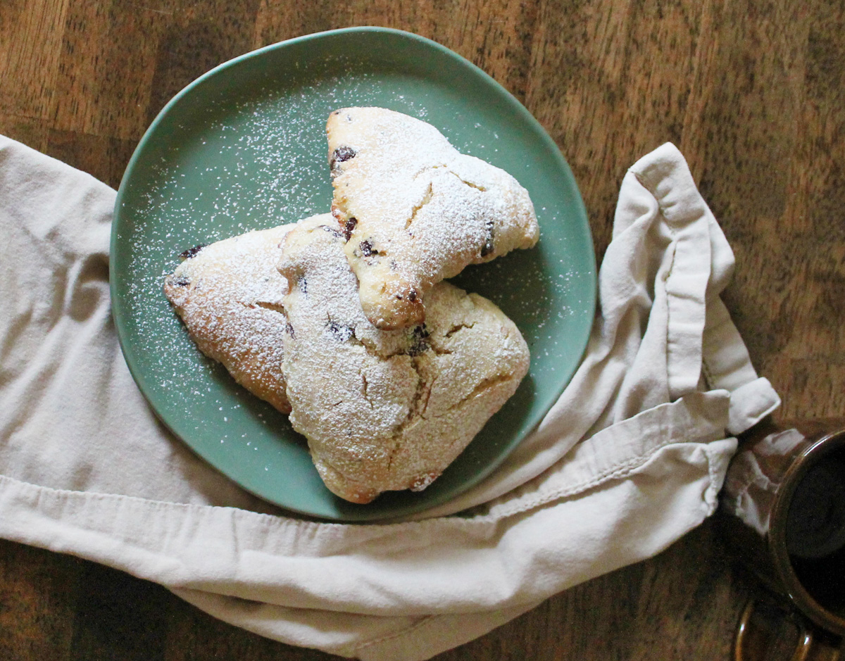 Overhead view of three orange scones piled on a light blue plate, surrounded by a light colored tea towel. A dark brown mug of tea sits to the side.