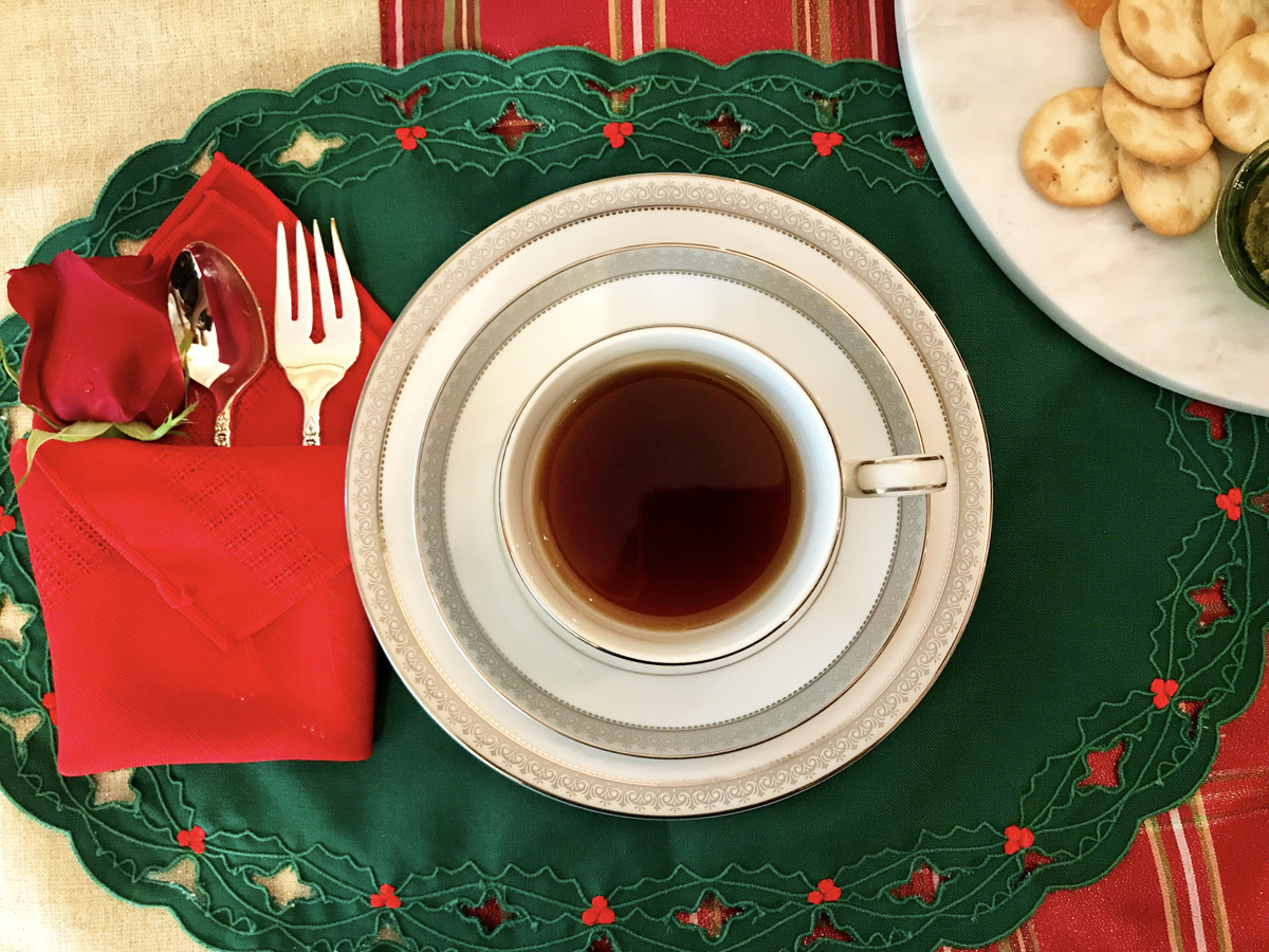 Overhead view of a place setting for a Christmas tea party featuring a white and silver teacup and saucer full of tea on a green placemat. A fork, spoon, and red rose and wrapped in a red napkin and placed to the left.