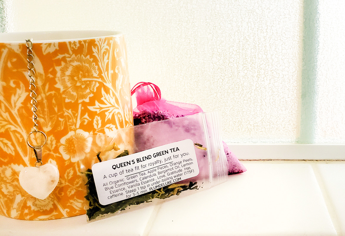 A yellow and while floral print mug, small bag of loose leaf green tea, and pink mesh bag sit on a white tile shelf.
