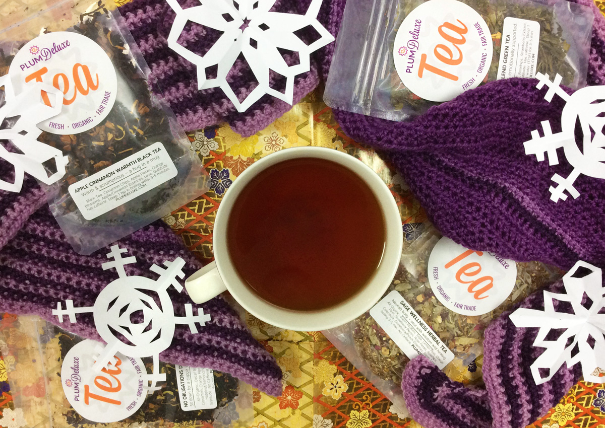 Overhead view of a mug of tea, purple crochet scarf, bags of Plum Deluxe loose leaf tea, and paper snowflakes arranged on floral wrapping paper.