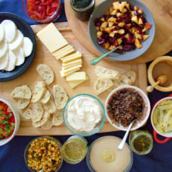 Overhead view of a table full of food for a bruschetta bar: bread, cheeses, tomatoes, salsas, hummus, and more.