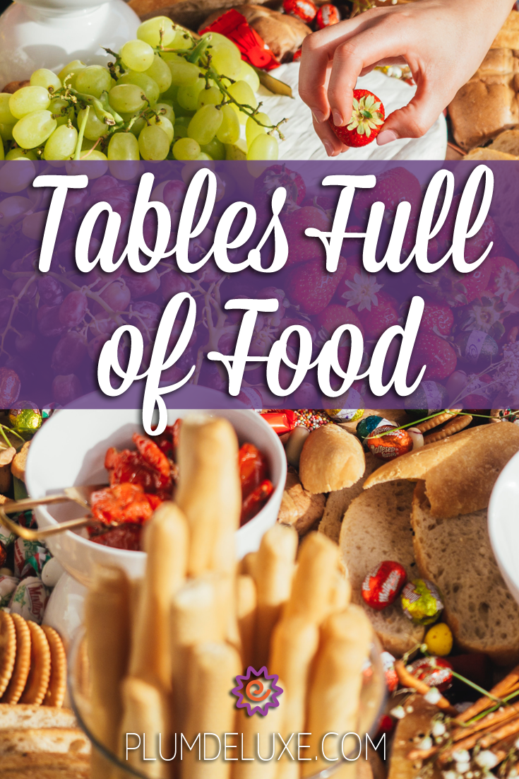 A hand reaches in to pluck a strawberry from a table full of food like fruit, cheese, and bread. The overlay text reads: Tables Full of Food.