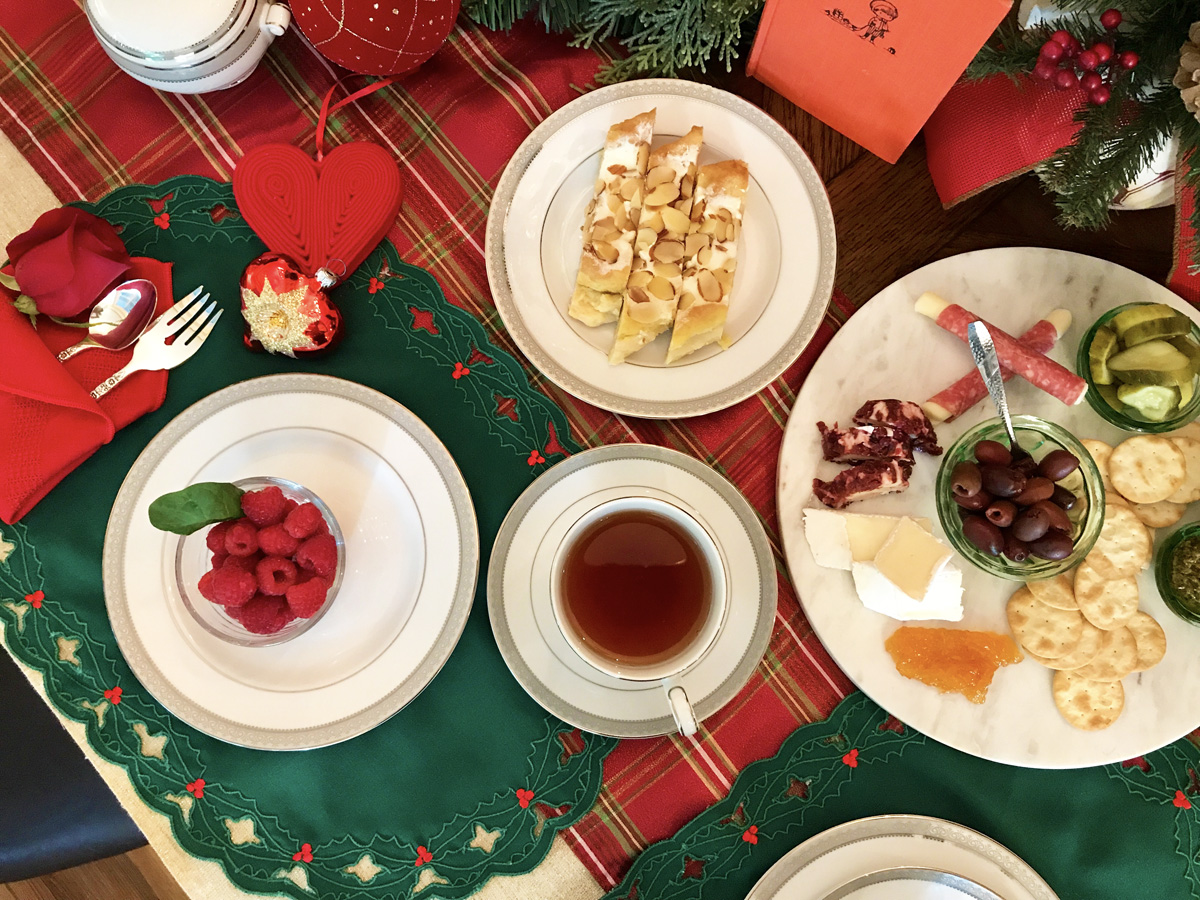 Overhead view of white dishes filled with raspberries, almond puff, and charcuterie and white teacups full of tea arranged on red and green linens.